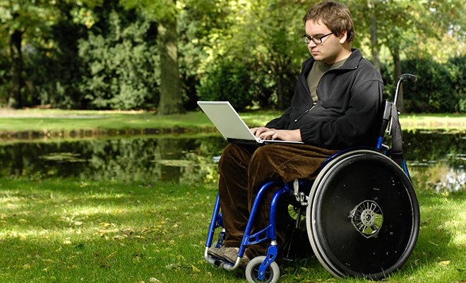 Young Man in a Wheelchair Working on His Laptop