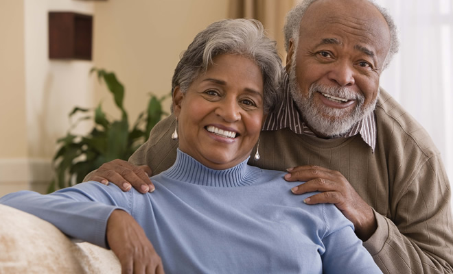 Senior African-American couple at home smiling.