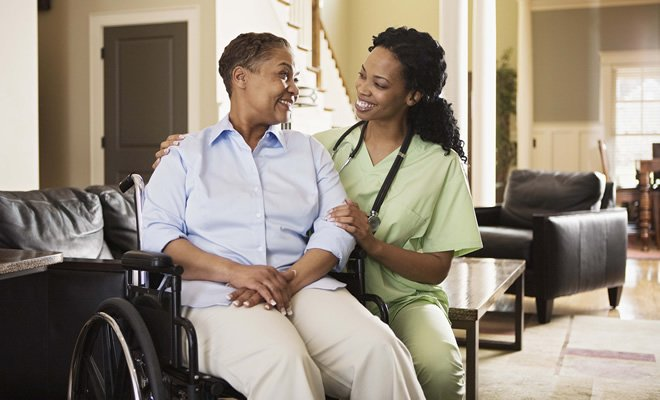 A woman in a wheelchair at home being assisted by a nurse.